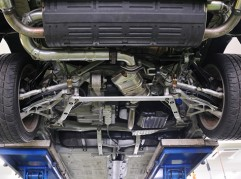 The undercarriage of an automobile showing metal struts connecting to the suspension system near each wheel